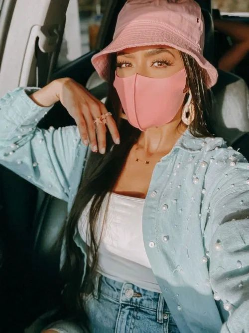 blue jeans, a white top, a blue pearl embellished shirt, a pink bucket hat and a matching face mask