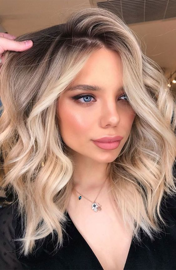 gorgeous rooty warm blonde wavy hair with mixed shades of blonde that looks very natural and very chic
