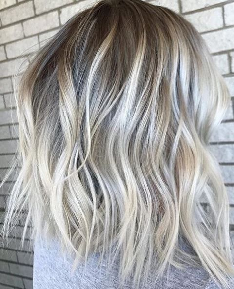 icy and rooty blonde hair with light waves on medium length hair is amazing