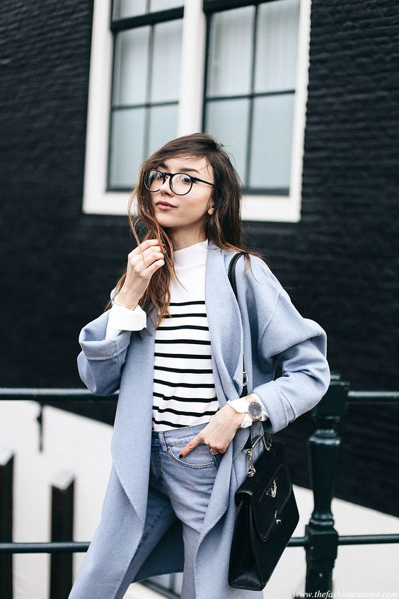 light blue jeans, a baby blue coat, a Breton stripe top and a black bag for a casual look