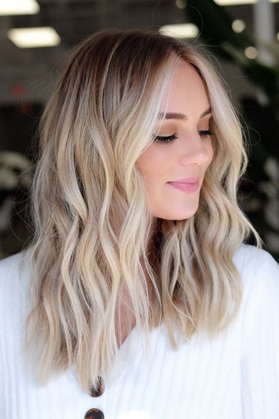 rooty blended blonde hair with light waves is a very beautiful and chic solution for now