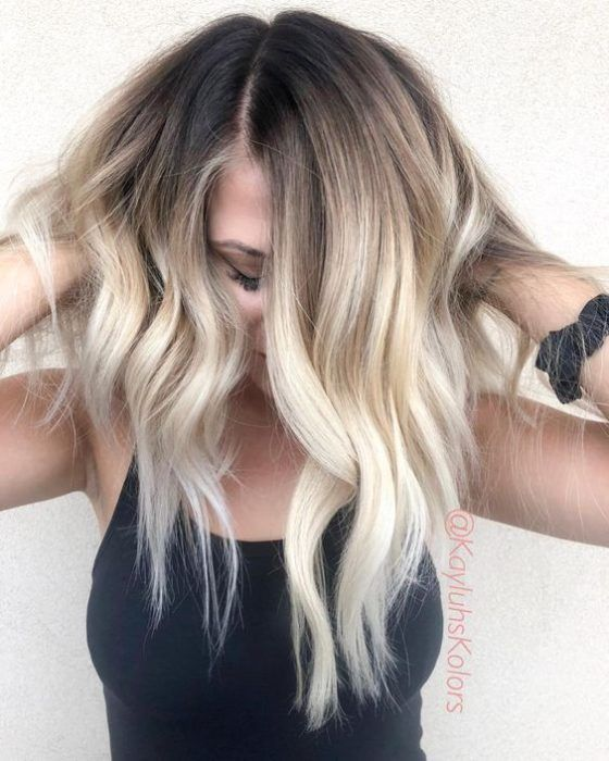 rooty bright blonde wavy hair is a bold idea with a soft transition between the hues