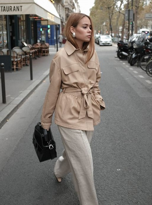 white linens trousers, a tan safari jacket with a sash, tan shoes and a black bag plus statement earrings
