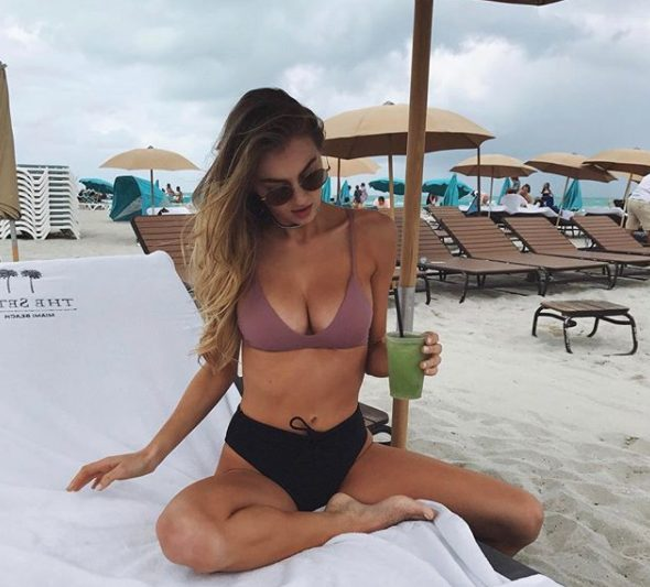 a simple swimsuit with a mauve top and a black high waisted bottom with a bow