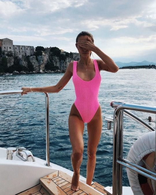 a neon pink one piece swimsuit with a deep neckline and thick straps and a high cut bottom is bold