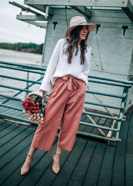 With beige hat, white loose sweatshirt and beige ankle strap high heels