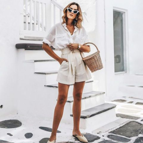 With beige high-waisted shorts, beige flat mules and straw bag