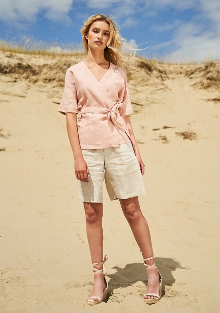 With beige linen shorts and beige lace up sandals