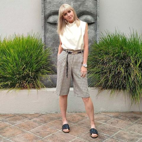 With beige sleeveless top and black flat sandals