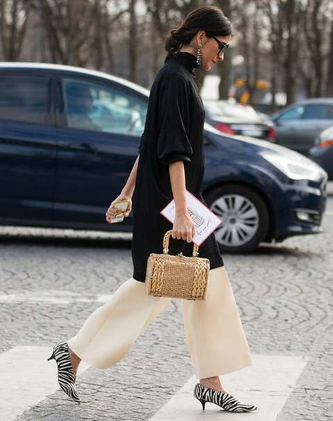 With black long turtleneck, beige palazzo pants and straw bag