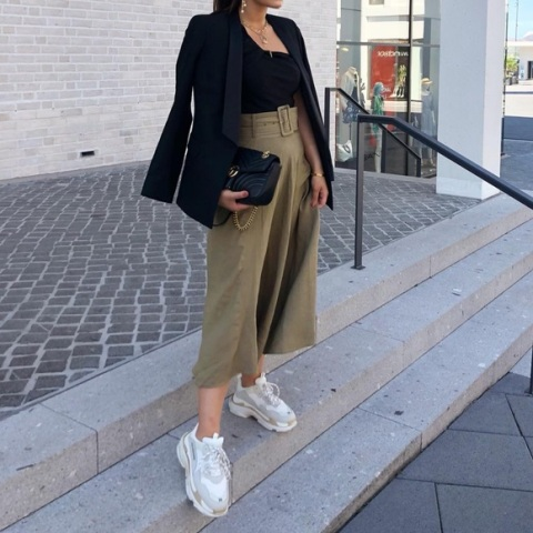 With black top, black blazer, chain strap bag and white and gray sneakers