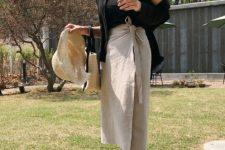 With black top, black cardigan, beige bag and hat