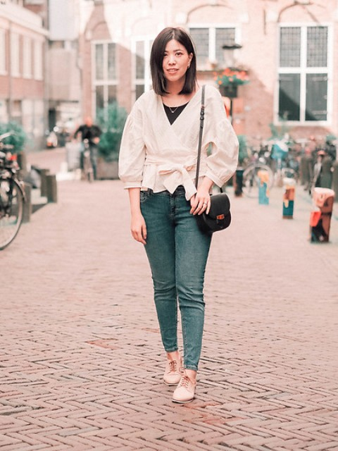 With black top, black leather bag, jeans and beige flat shoes