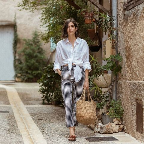 With checked trousers, straw tote bag and brown sandals