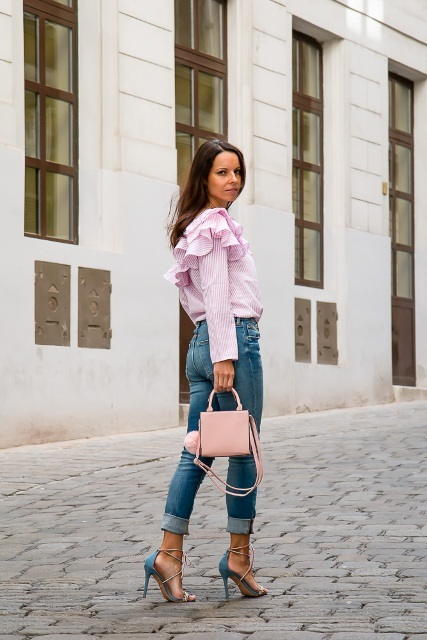 With cuffed jeans, pale pink mini bag and blue and pale pink lace up high heels