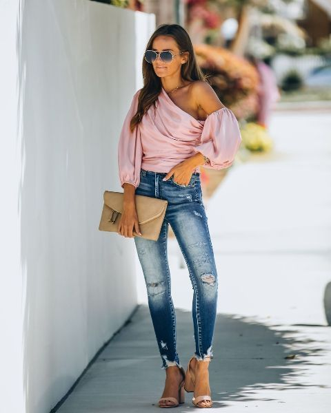 With distressed skinny jeans, beige clutch and beige sandals