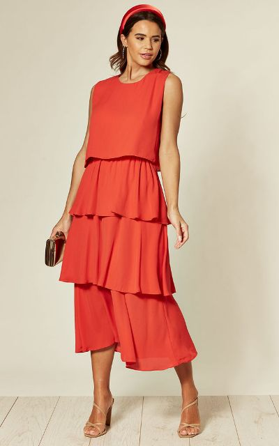 With golden clutch, beige sandals and red headband