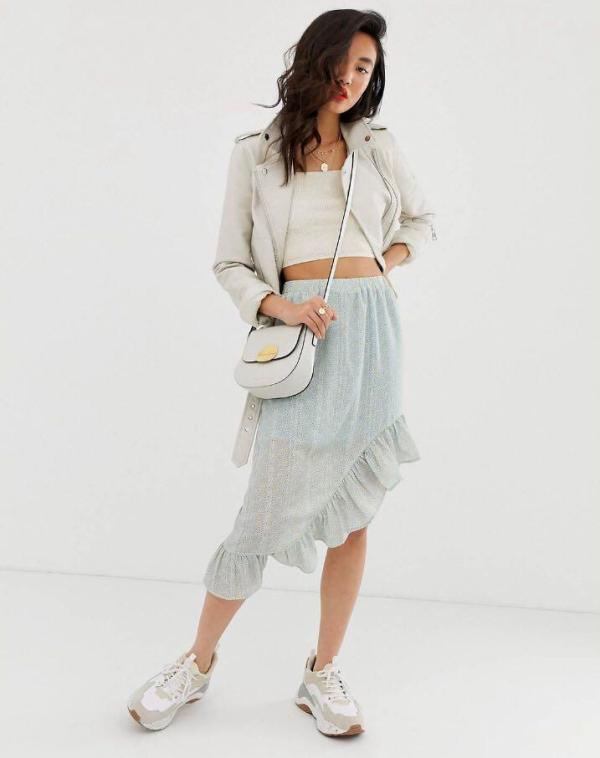 With gray jacket, crop top, crossbody bag and sneakers