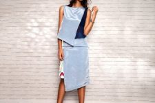 With light blue and navy blue asymmetrical top and black shoes