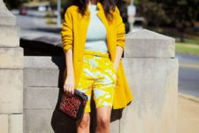 With light blue shirt, yellow coat, leopard printed clutch and light blue pumps