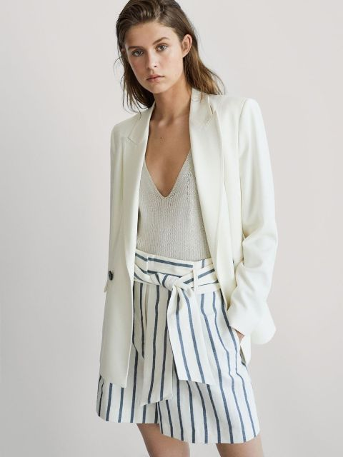 With light gray V neck top and white long blazer