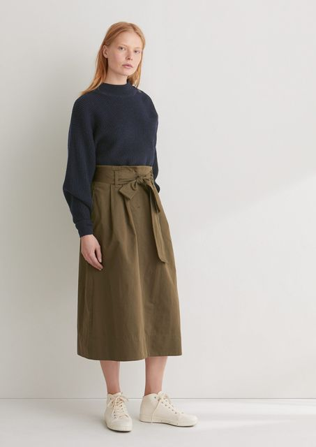With navy blue sweatshirt and beige lace up shoes