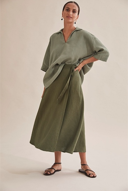 With olive green loose shirt and black flat sandals
