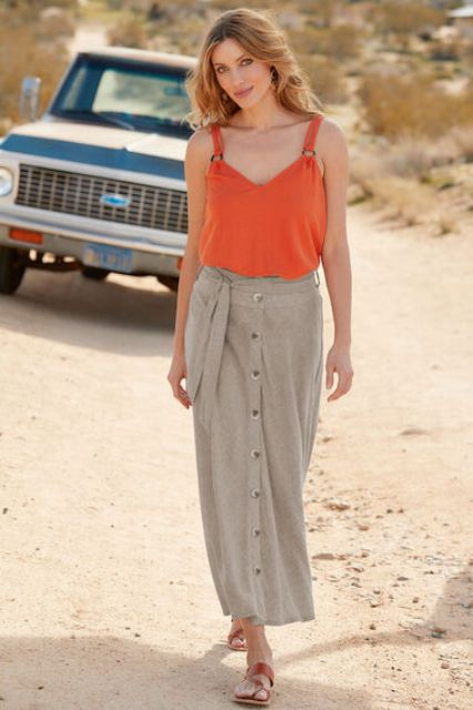 With orange sleeveless top and brown flat sandals