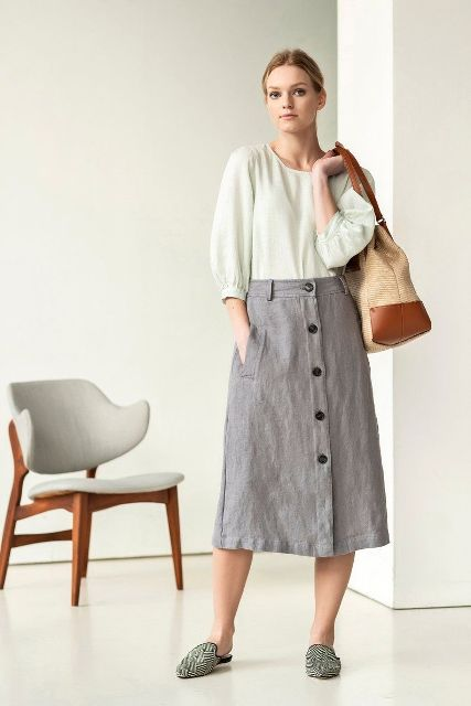 With pastel colored blouse, beige and brown tote bag and printed flat mules