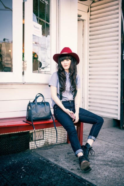 With red hat, button down short sleeved shirt, black lace up boots and bag