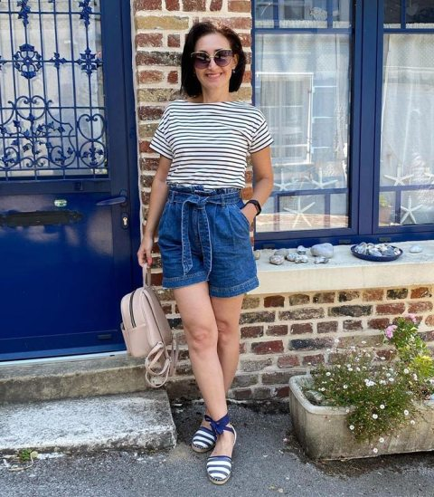 With striped t shirt, beige leather backpack and white and navy blue striped flat shoes