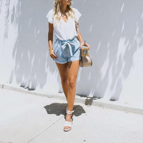 With white V-neck shirt, beige bag and white ankle strap shoes
