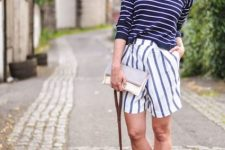 With white and navy blue striped shirt, clutch and beige pumps