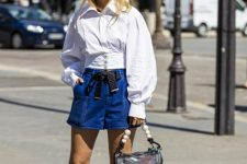 With white blouse, transparent bag and white and blue low heeled shoes