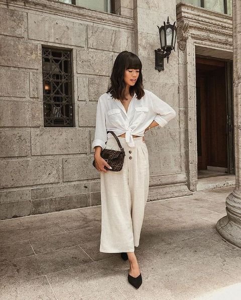 With white button down shirt, printed bag and black mules