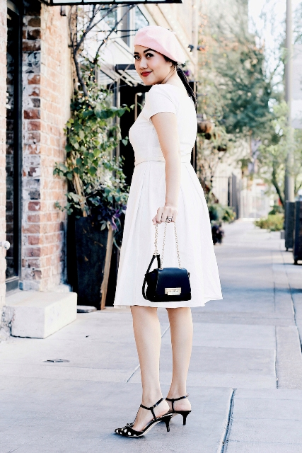 With white knee length dress, pale pink beret and black chain strap bag