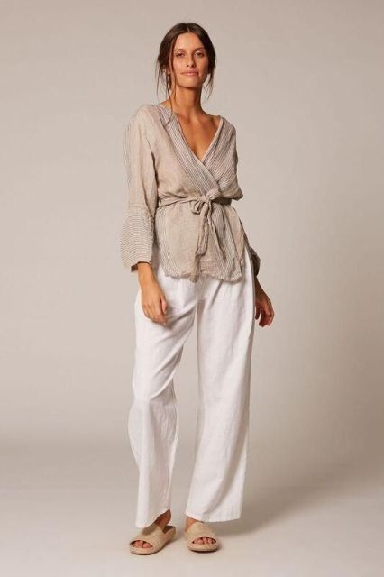 With white loose trousers and beige flat sandals