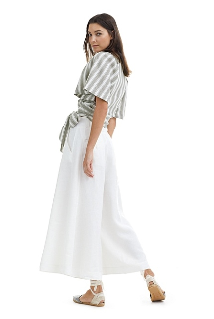 With white palazzo pants and white lace up flat sandals