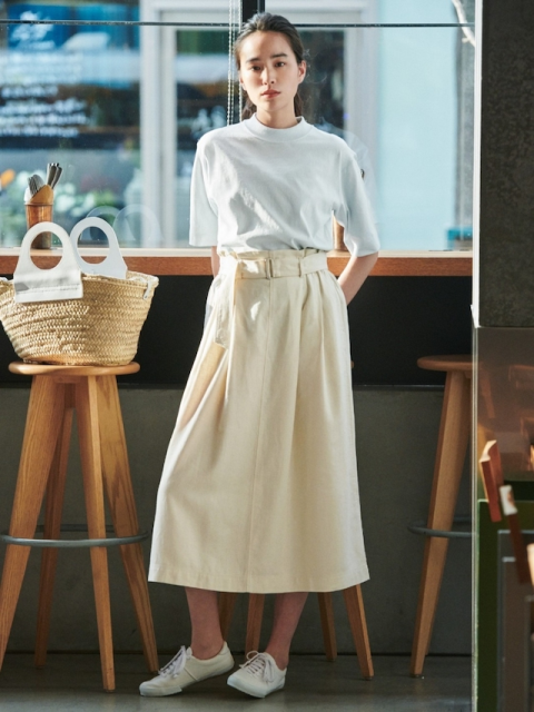 With white shirt, straw tote bag and white flat shoes