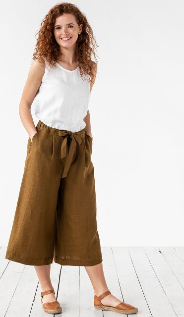With white sleeveless top and brown leather sandals