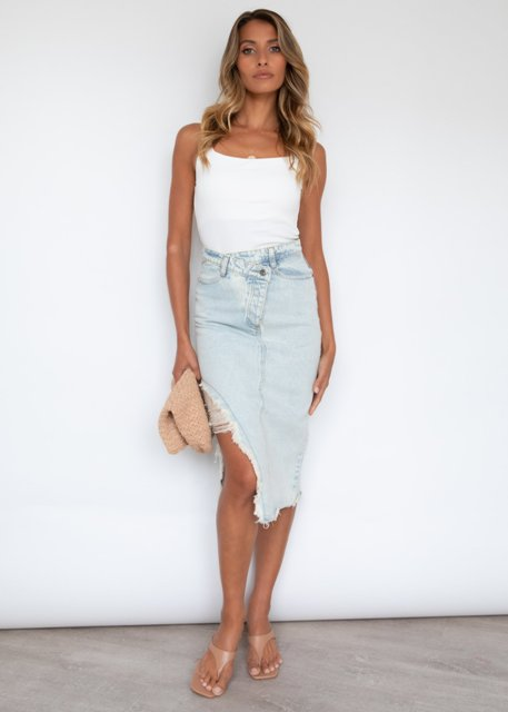 With white top, beige sandals and clutch