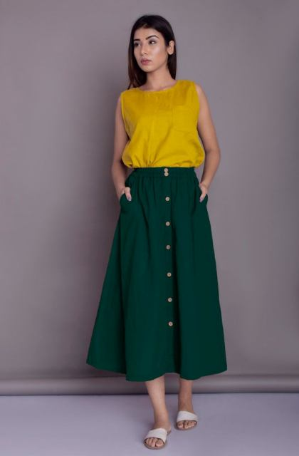 With yellow sleeveless top and white flat sandals