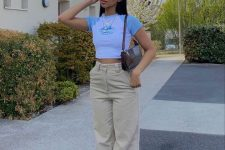 a 90s inspired look with a color block cropped tee, tan high waisted pants, white trainers and a baguette bag
