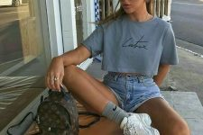 a 90s inspired outfit with a cropped t-shirt, blue denim shorts, white trainers and grey socks plus a brown backpack