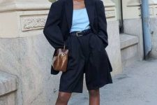 a black Bermuda short suit with an oversized blazer, a light blue top, nude heels and a brown bag