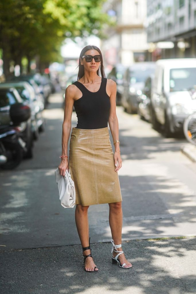 a black bodysuit, a tan leather-looking knee skirt, lace up sandals of mismatching colors and a clutch