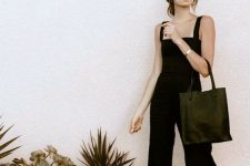 a black jumpsuit on thick straps, black heels and a tote plus sunglasses for a night out look