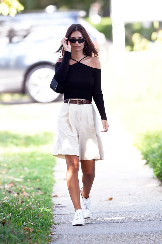 a black off the shoulder top with straps, white bermuda shorts, white sneakers and a brown belt