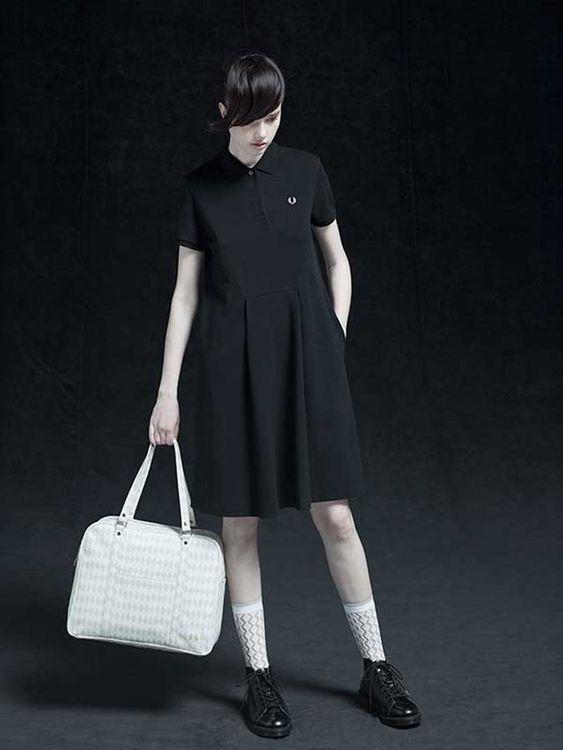 a black polo dress with a pleated A-line skirt, white socks, black shoes and a retro white bag
