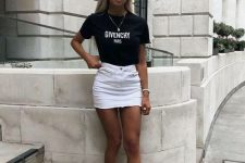 a black printed cropped t-shirt, a white denim mini, pink trainers and sunglasses for a sexy look